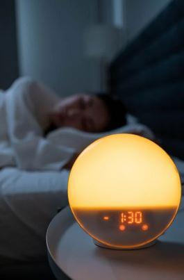 Woman sleeping soundly with alar clock at 1:30 visible.